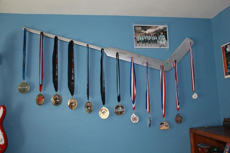 My husband made this to display my son's first season of travel hockey medals.
