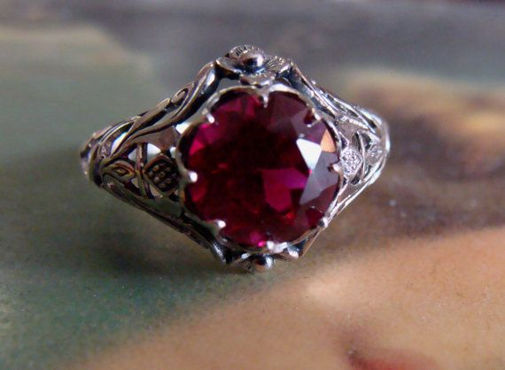 Here is a lovely Art Nouveau design sterling silver Ruby ring. It is size 5.75. It has a 2 ct lab created round cut Ruby stone , surrounded by flowers and vines designed in to the silver. It is hallmarked on the inside 925. The top measures 5/8 inch north to south and narrows to the back. This ring is a real eye-catcher!....it would make an excellent gift for yourself or someone special.     A BIT OF HISTORY After serving in World War 2, Guy James opened a jewelry store in East Tennessee...
