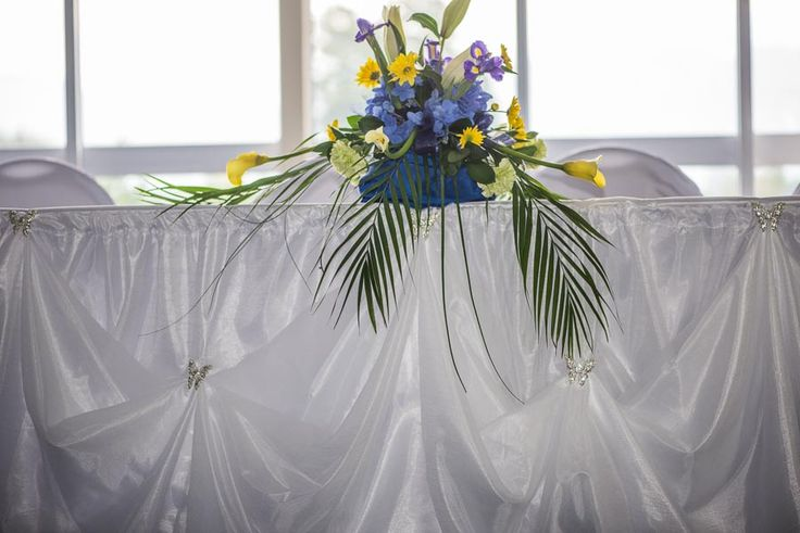 Blue and yellow on a butterfly brooch draped head table skirt
