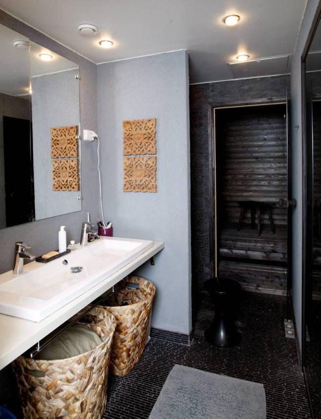 Tumma sauna on kylpyhuoneen jatkeena. Pyykit kerätään punottuihin koreihin.