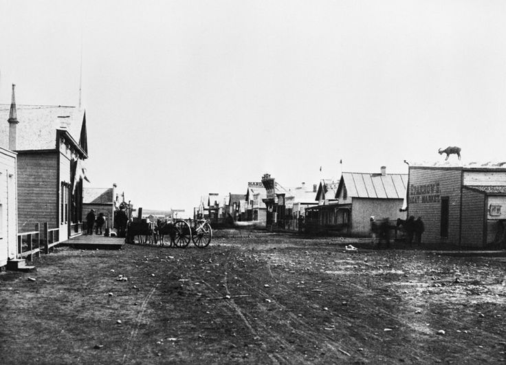 Stephen Avenue, looking east from McTavish (Centre) Street, Calgary, Alberta, ca. 1884-1885. Sparrow's Meat Market is in the right foreground and the North-West Mounted Police barracks in the background at end of street. (Glenbow Archives NA-660-1)