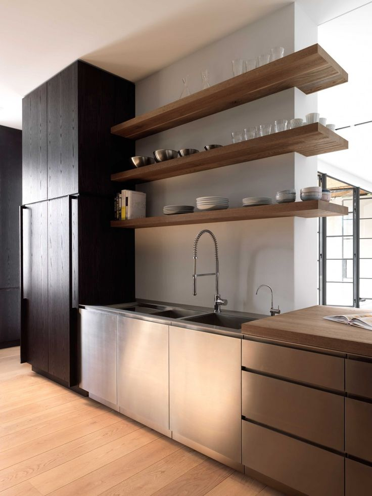 The mixture of materials in this kitchen complement each other perfectly. Stainless steel, an ebony stained hidden refrigerator, and even a wooden butcher block counter--I'm ready to renovate my kitchen now!
