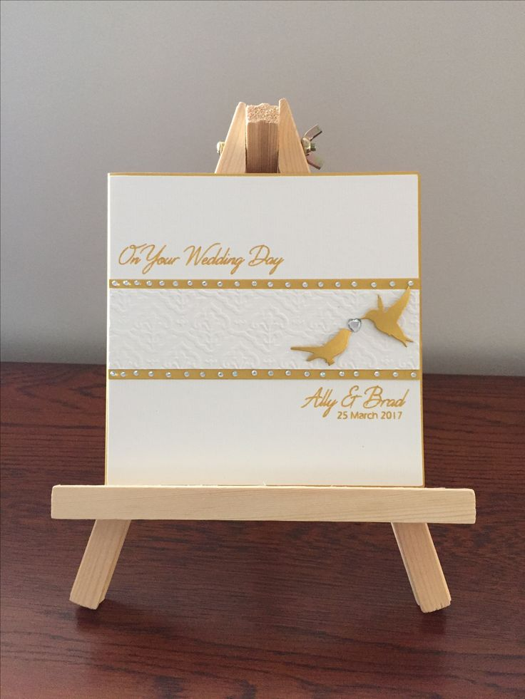Wedding card in white and gold. Two love birds with a diamanté heart