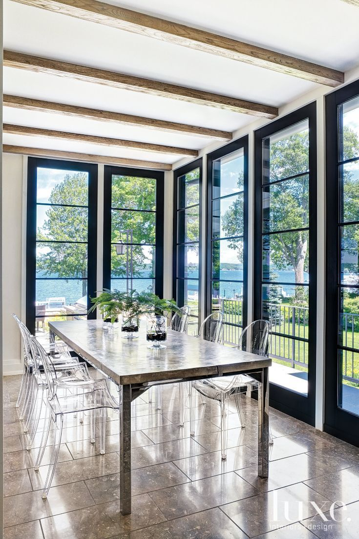The informal dining area features a custom cotto-pesto tabletop from de Giulio Kitchen Design. Louis Ghost chairs, by Philippe Starck for Kartell, are from Design Within Reach and provide unobstructed views of Geneva Lake.
