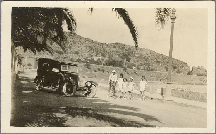 [Cuatro niñas y un niño en bicicleta junto a un automóvil antiguo : Benicasim]. (s.a.) - Anónimo