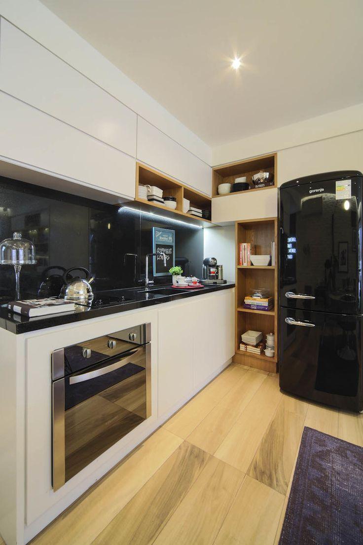 Cozinha preta e branca, com um toque delicado de madeira clara.