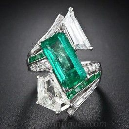 Spectacular Vintage Emerald and Diamond Cocktail Ring - This dynamic, large-scale ring is designed around a bright green elongated emerald-cut emerald weighing 4.00 carats, which is asymmetrically framed by two large fancy-cut diamonds: a 2.25 carat epaulet-cut diamond and a 1.75 carat trapezoid-cut diamond.  This truly magnificent, one-of-a-kind showstopper measures just a tad shy of 1 1/4 inches long. Wow!