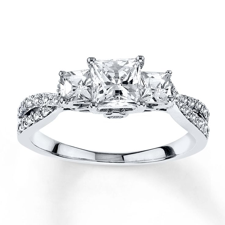 Three princess-cut diamonds stylishly grace the top of this engagement ring for her. Round diamonds add even more sparkle to the band for a diamond weight totaling 1/2 carat. The ring is crafted in lustrous 14K white gold. Diamond Total Carat Weight may range from .45 - .57 carats.
