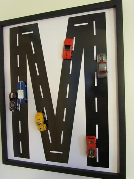"""Create some art for your little guys room! Take a large frame, and remove the glass. Cover the back board in white paper.. and cut a large initial out of black construction paper. Add some white lines with either thin tape, or paint.. and hot glue the cars on the """"road"""".. Fun!!"""