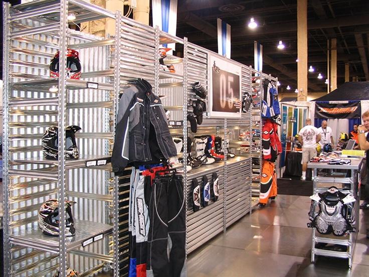 Ejemplo de estanterías metálicas industriales usadas como expositor en tienda de complementos de motos. Materiales estándar combinados para expositores y mostradores.   https://www.esmelux.com/galeria-de-shopfitter