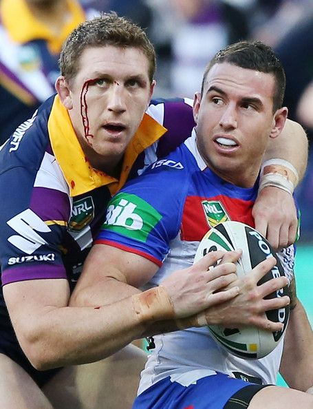 Darius Boyd of the Knights gets tackled by Ryan Hoffman of the Storm during the round 14 NRL match between the Melbourne Storm and the Newcastle Knights at AAMI Park on June 16, 2013 in Melbourne, Australia.