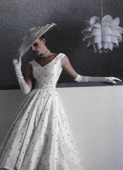 CANDY Robe vintage, années 50 new-look en doupion de soie ivoire rebrodé de pois gris/taupe. Décolleté en v. Ceinture drapée. Noeud deux pans dans le dos. Longueur mi mollets. Accessoires : gants longs en satin de soie, chapeau DIANE, en doupion de soie drapé.