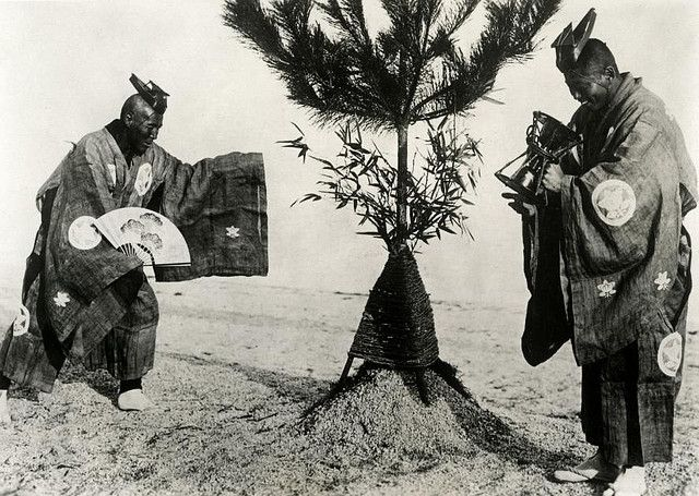 Japanese custom on New Year's Eve, monks in traditional costumes count the last seconds of the old year with an hourglass and welcome the new year by honouring fresh green leaves on a bush. Japan, [1932].