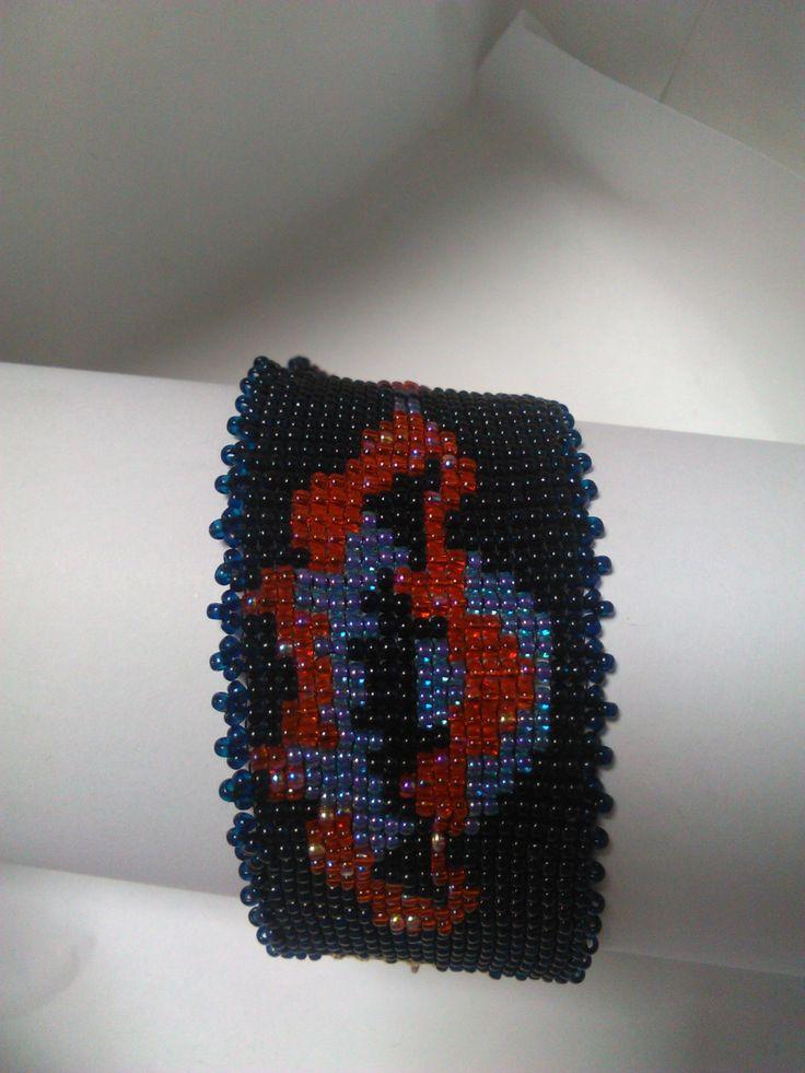 Čajové konvičky Náramek, kde základ tvoří hodně tmavě modrá a vzor je v barvách modro-fialové a oranžovo-červené. Délka náramku je cca 20cm, šířka jsou 4cm. Zapínání je na karabinku.