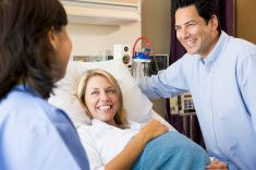 Doctor Talking To Pregnant Woman And Her Husband stock photo