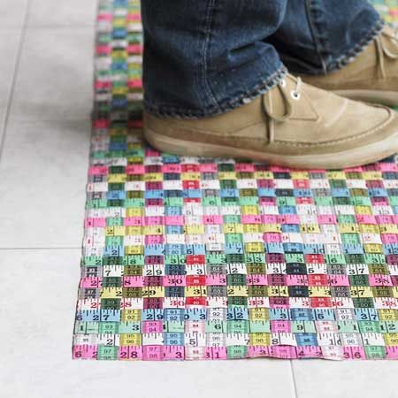 Mat made out of woven ribbon tape measures.