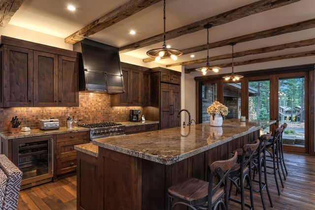 Photo of a rustic kitchen in Sacramento.This is an example of a rustic galley eat-in kitchen in Sacramento with shaker cabinets, dark wood cabinets, brown backsplash, mosaic tile backsplash, paneled appliances, dark hardwood floors and an island.Design ideas for a rustic home design in Sacramento.This is an example of a rustic two-story exterior in Sacramento with wood siding and a gable roof.Inspiration for a rustic living room in Sacramento.Rustic living room in Sacramento.This is an…