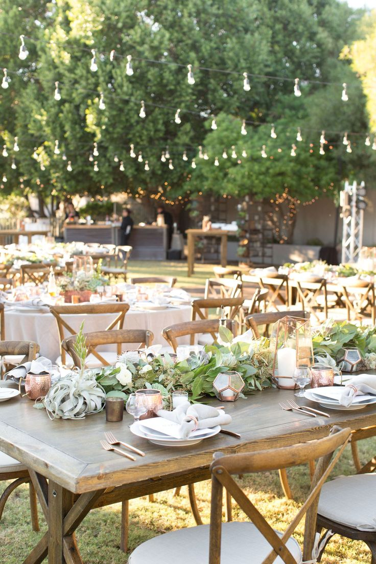 Gorgeous desert wedding at a private estate in Paradise Valley, Arizona. The bride wore a simple tea-length gown and strappy nude heels. She carried a stunning bouquet made almost exclusively of succulents. And all of the  reception and wedding decor was greenery made of succulents, cacti, and eucalyptus table runners, set against natural wood tables, chairs, and backdrops.