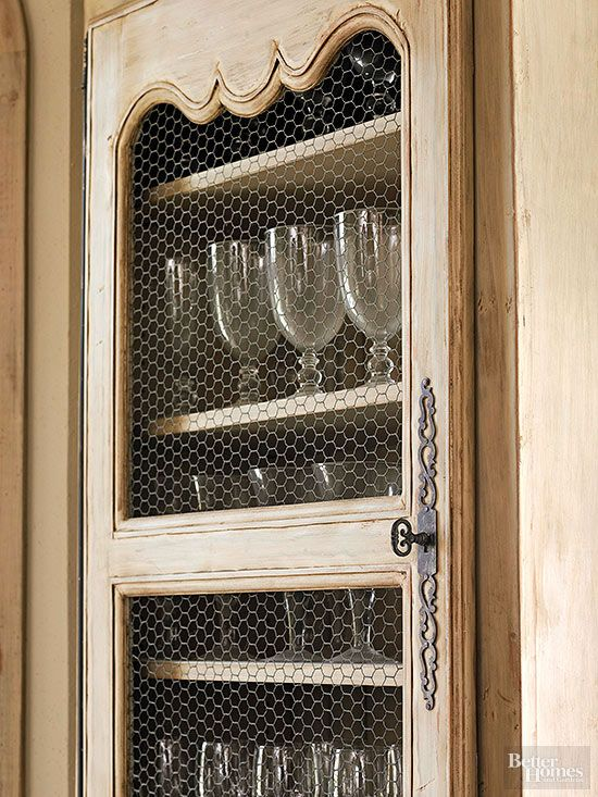 Instead of glass, chicken-wire mesh brings a country French detail to the upper cabinets. Along with the furniturelike cabinets and a mix of finishes, details such as chicken wire inserts create an unfitted look that furthers the French aesthetic.