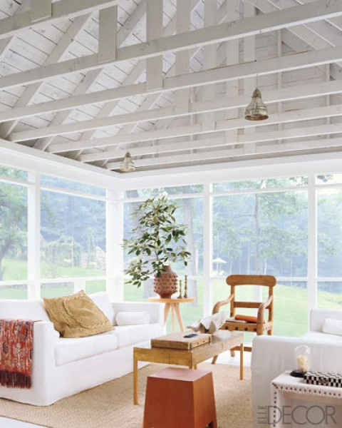 Room/Style: Family Room, Modern    Notes: In this sunroom in Washington, Connecticut, IKEA sofas are grouped with a gold-leafed cocktail table by homeowner Stephen Piscuskas, a tripod side table and Douglas-fir stool by York Street Studio, and a vintage armchair from Duane.    Photographer: Miguel Flores-Vianna  Featured in: A Country Home Goes Modern  Issue: June 2010