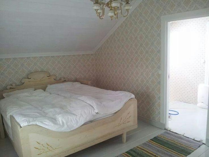 Gammaldags sovrum med kökssoffa som säng. Tapet Dellen.