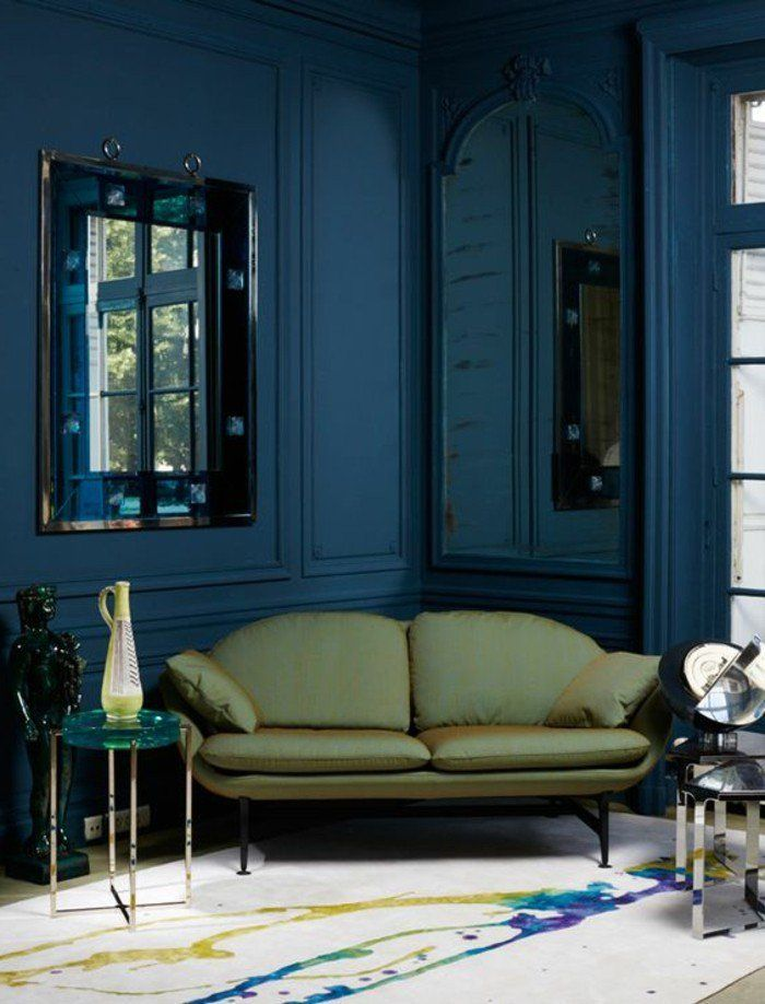 canapé en jaune foncé, murs bleus foncés, tapis design chic, miroir mural