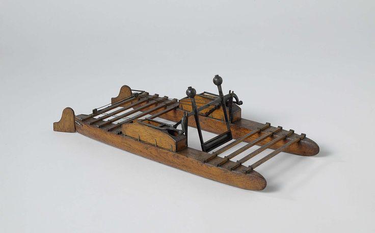 T. van den Bosch | Model van een prototype estafettevaartuig, T. van den Bosch, 1820 - 1858 | Model van een op handkracht voortbewogen catamaran. De twee drijvers zijn met latten aan de uiteinden aan elkaar verbonden en hebben elk een plaats voor een bestuurder. Het voorbewegingsmechanisme bestaat uit een enkel scheprad met contra-gewichten, door middel van handvaten aan elke kant in beweging gebracht. Beide drijvers hebben een roer, waarvan de helmstokken met een scharnierende stang aan…