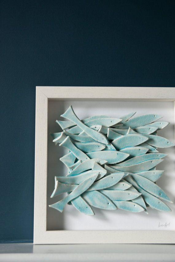 Houd er rekening mee dat de regeling van vis varieert van tegel aan tegel, de fotos vertegenwoordigen de algemene ontwerp en kleur afwerking ..............................................................  school van licht turquoise vissen, ingelijste 3D-keramische illustraties  gebeeldhouwd volledig met de hand, waar elke één vis is gesneden, gladgestreken en individueel ingericht op een tegel, geglazuurd in lichtblauw met mooie craquelé effect; de kunst tegel komt in een eenvoudige witte…