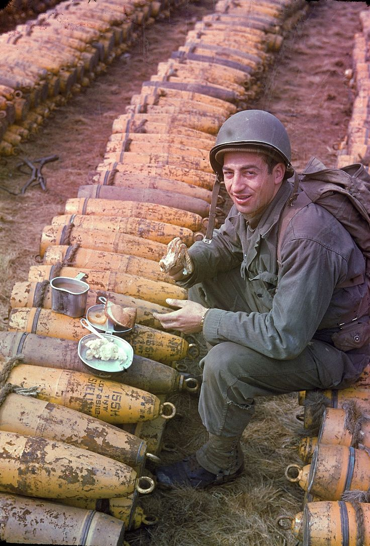 An unidentified American soldier sits and eats his meal (which includes chicken, mashed potatoes, bread, and pineapple) atop rows of a stockpiled ammunition shells, England, May 1944.