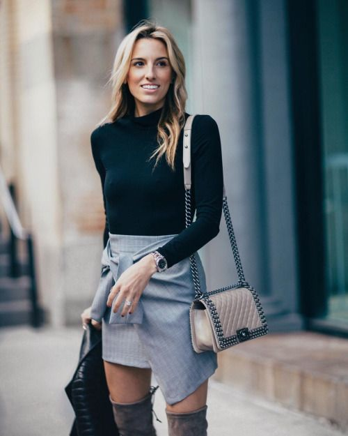 Black turtleneck and gray asymmetrical skirt