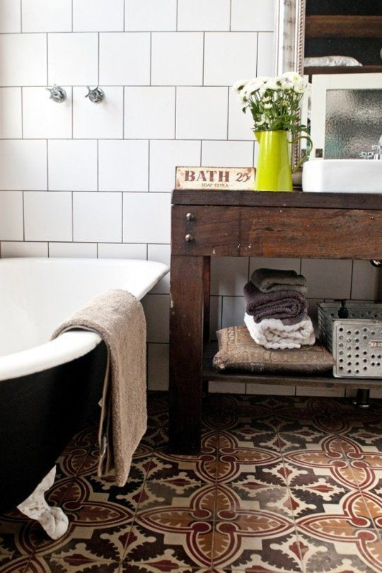 I love the mix of styles here: the graphic tile floor, white tiled walls, black tub, and rustic wooden vanity.