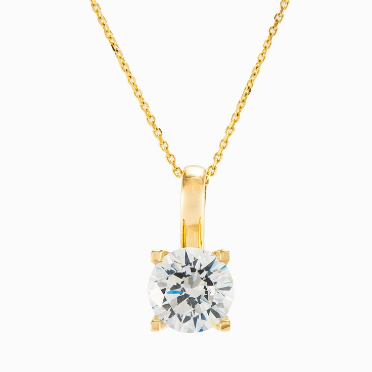 Elegant, soitaire gold pendant made in 14k yellow gold. The pendant is dominated by a white cental crystal. The chain is not included.