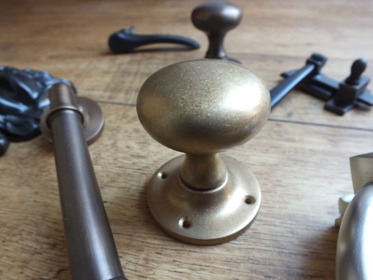 A cushion door knob, shown in the aged brass finish. On the left of this is an antique brass door handle. British made and made and finished by hand, this vintage door hardware is available to buy at - http://www.britishironmongery.co.uk/shop/cushion-door-knob/823.htm