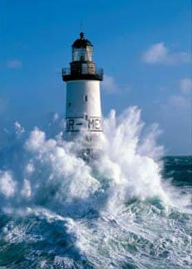 Olas estrellándose contra un faro que muestra el poder del mar