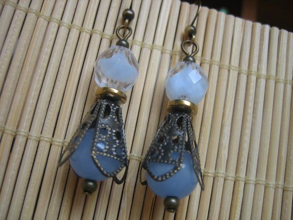Antiqued brass filigree bead caps and small brass beads pull together these pale blue swirled crystal and translucent blue glass beads. Nickel free brass fish hook ear wires make these lightweight earrings comfortable enough to wear every day, and they come with small stoppers to keep them firmly in place.  $25.00