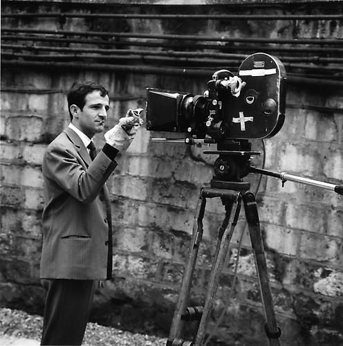 Francois Truffaut, cigarette in his mouth, standing in front of an Éclair CAMEFLEX CM3 camera holding a hand puppet in front of the lens 1961 by Raymond Cauchetier