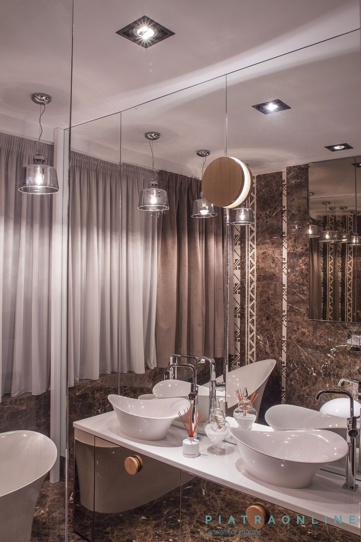 En suite bathroom of a modern apartment. Elegant design. Walls cladded with Maron Emperador marble and a Burdur Beige and Maron Emperador decorating border. Countertop made of Thassos marble. Apartment in Bucharest, Romania.