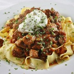 This recipe for Hungarian stew made with pork loin and bacon is seasoned with paprika and served over egg noodles.