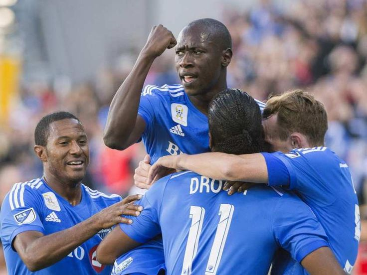Montreal Impact's Didier Drogba (11) celebrates with teammates, from left, Patrice Bernier, Hassoun Camara and Wandrille Lefevre after scoring against D.C. United during first half MLS soccer action in Montreal, Sept. 26, 2015.