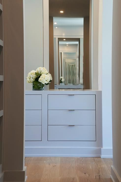 Gray walk in closet features a built-in gray dresser with inset drawers under a taupe mirror.