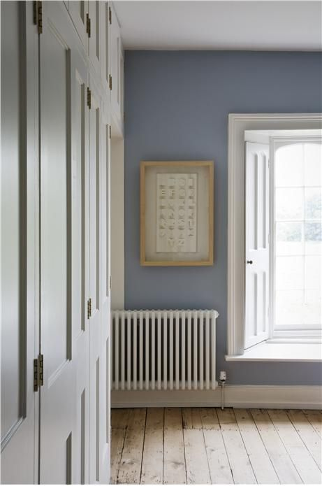 A bedroom with walls in Lulworth Blue Estate Emulsion and woodwork/ceiling in Wimborne White Estate Eggshell and Estate Emulsion.