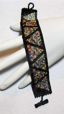 Brightly colored seed bead triangles adorn this peyote bracelet. Triangles surrounded by bright black seed beads and beaded toggle/loop closure. Bracelet measures 1 wide and length is made to order. Upon purchase, send a note with the length desired. $30.00 USD