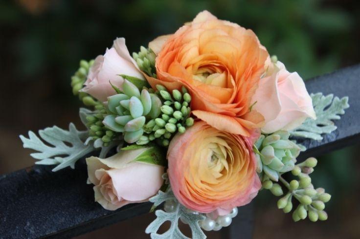 peach/coral wrist corsage features dusty miller, ranunculus, sedum, mini roses, seeded eucalyptus and succulents