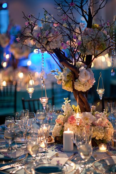 Wedding centerpieces with branches & hanging tea light holders.