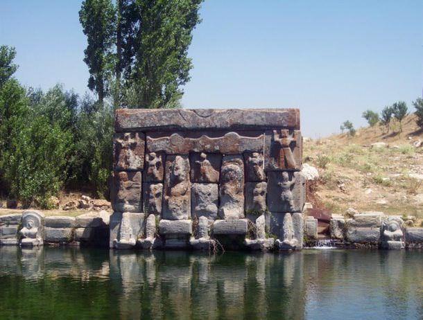 Bir yüzü yüksek kabartma figürlerle bezelidir. Kompozisyonun merkezinde yer alan bakışık ve dikey konumlu iki blokta oturur durumda bir tanrıyla bir tanrıça bulunur.