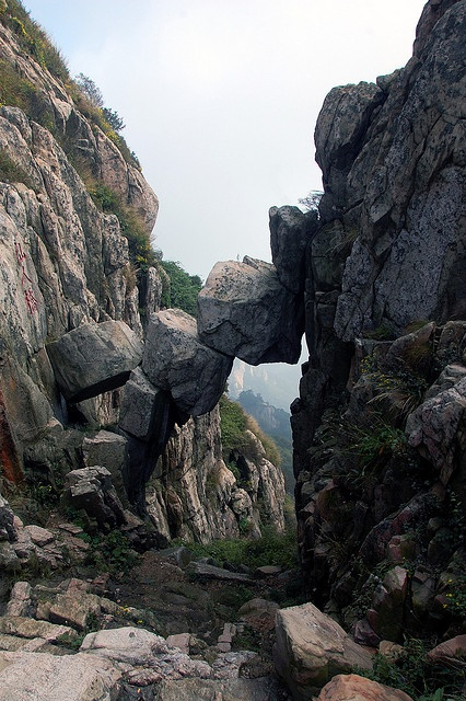 The Immortal Bridge, Mount Tai in the Shandon Province, is composed of three huge rocks and several smaller ones. Below it is a valley and to the south is a seemingly bottomless abyss. No one knows quite when these enormous rocks fell in to their current place but it is quite likely they have been like this since the last ice age.