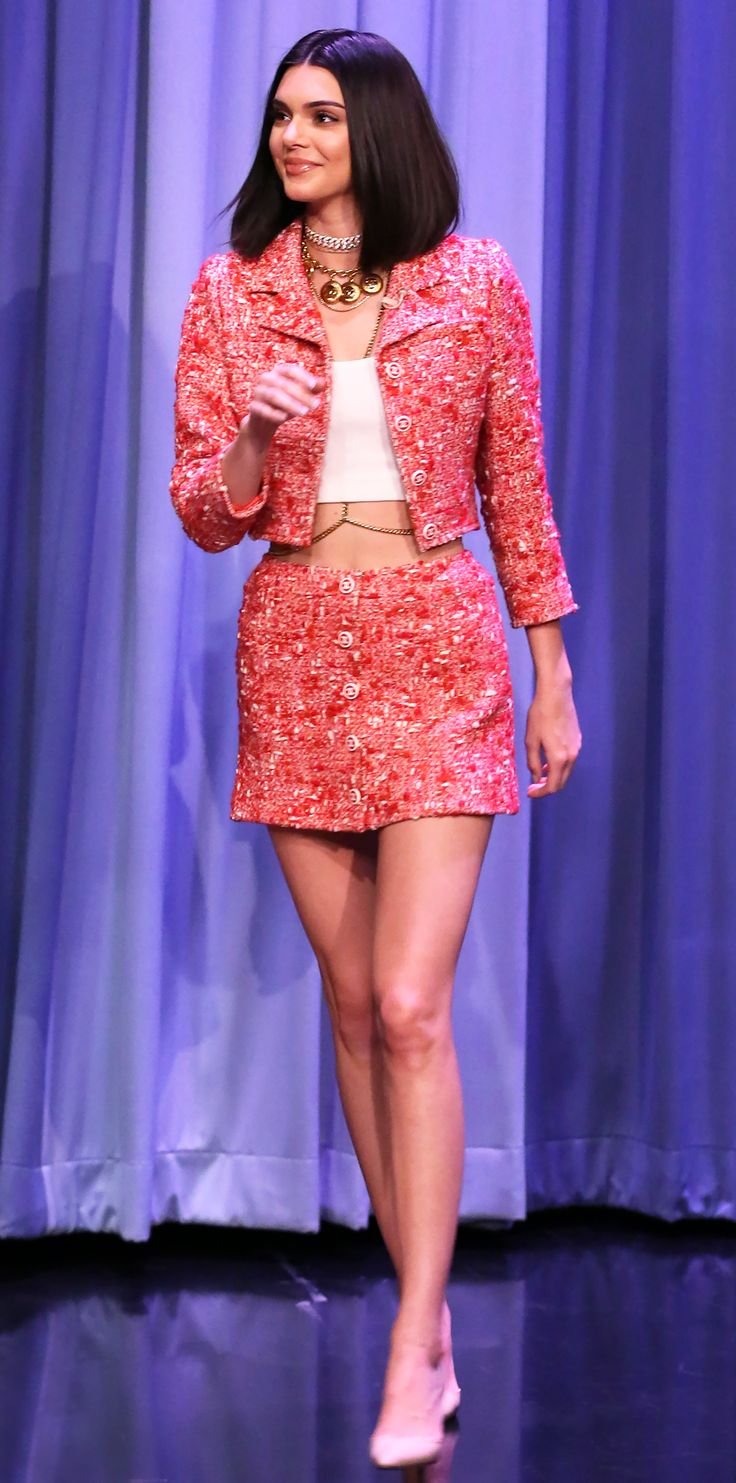 Kendall Jenner appeared on The Tonight Show Starring Jimmy Fallon in a sweet and flirty number. The model wore pink boucle coordinates, a tiny crop top, and gold jewelry (we see that body chain!). KJ's MO: layer on heavy metal hardware to toughen up any outfit.