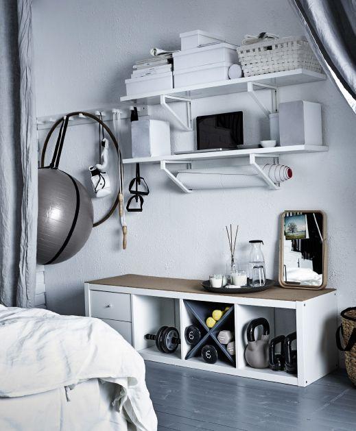 Equipamiento de fitness almacenado en la pared de un dormitorio con perchas y baldas.