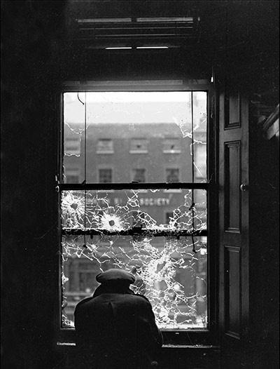 An Irishman looking through a bullet-riddled window pane during the Irish Civil War. Dublin, 1922. Photo by Walter Doughty.