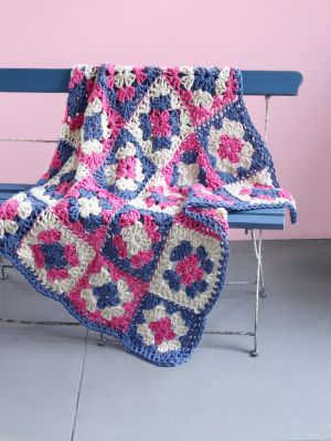 This beautiful granny afghan features a simple floral style square. Crochet with our Hometown USA yarn to brighten any room with colors that pop.